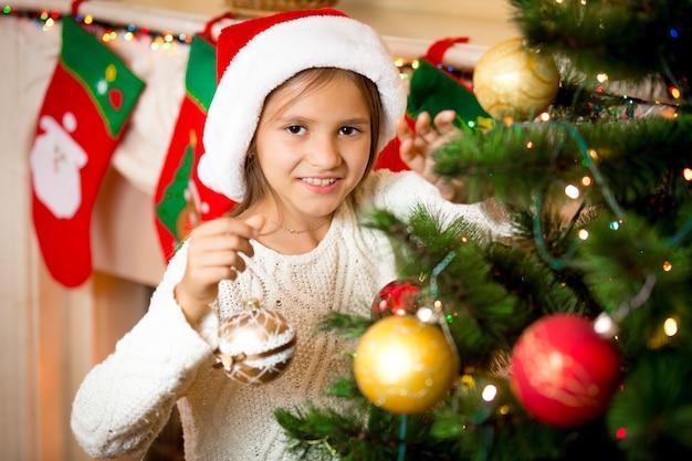 Nahaufnahmeporträt des netten lächelnden mädchens, das weihnachtsbaum mit goldenen kugeln verziert