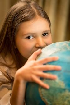 Nahaufnahmeporträt des netten mädchens, das hand auf globus hält