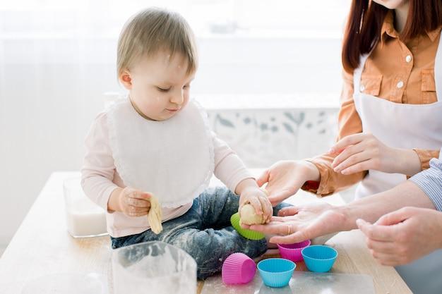 Nahaufnahmeporträt des niedlichen kleinen mädchens, das auf dem esstisch sitzt und mit teig zum backen von muffins in farbigen formen spielt. mutter und großmutter arbeiten mit teig. muttertagskonzept