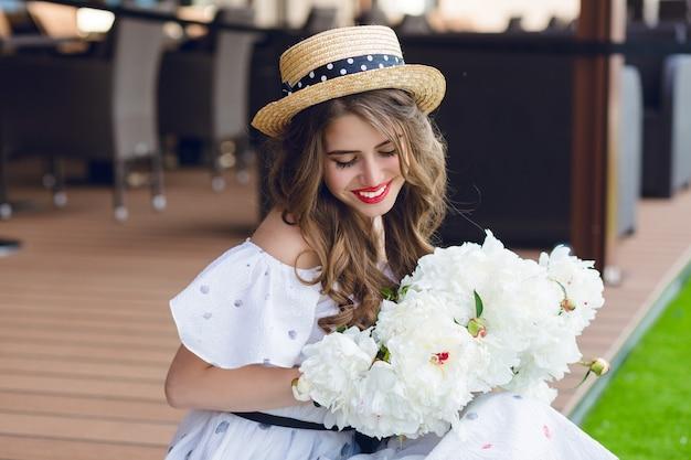 Nahaufnahmeporträt des niedlichen mädchens mit dem langen haar im hut, das auf boden auf der terrasse sitzt. sie trägt ein weißes kleid mit nackten schultern und rotem lippenstift. sie hält weiße blumen in den händen.