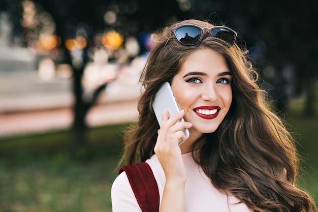 Nahaufnahmeporträt des niedlichen mädchens mit effektivem makeaup und langen haaren, die am telefon im park sprechen. sie hat weinige lippen und lächelt.