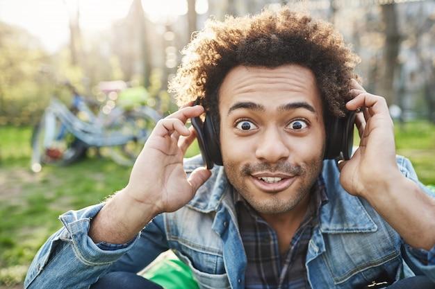 Nahaufnahmeporträt des niedlichen modischen afroamerikaners, der mit geknallten augen schaut und augenbrauen an der kamera anhebt, während er im park sitzt und musik über kopfhörer hört und aufregung ausdrückt