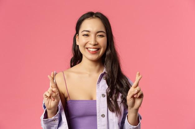 Nahaufnahmeporträt des optimistischen glücklichen, lächelnden asiatischen mädchens, das glauben hat, alle gut sein, daumen drücken, viel glück, lachen, hoffnungsvoll positive ergebnisse vorwegnehmend