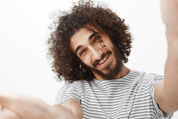 Nahaufnahmeporträt des positiven gutaussehenden emotionalen kerls mit bart und stilvollem lockigem haarschnitt, hände in richtung ziehend