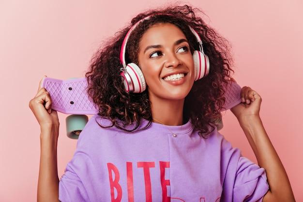 Nahaufnahmeporträt des positiven weiblichen modells im lila hemd, das oben mit lächeln schaut. schöne afrikanische junge dame, die lieblingslied in den kopfhörern hört.