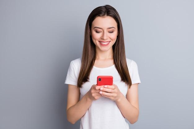 Nahaufnahmeporträt des reizenden süchtigen fokussierten fröhlichen mädchens, das telefon verwendet
