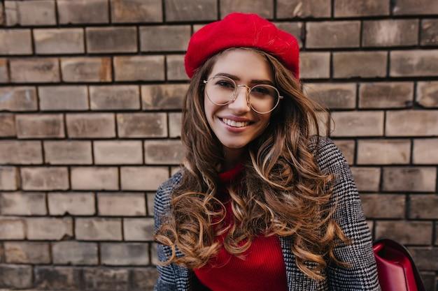 Nahaufnahmeporträt des romantischen französischen mädchens in der netten roten baskenmütze, die mit lächeln auf städtischem hintergrund aufwirft