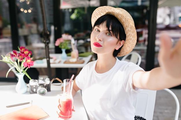Nahaufnahmeporträt des romantischen mädchens mit blasser haut und dunklem haar, das im gemütlichen straßencafé mit blumen auf tisch kühlt