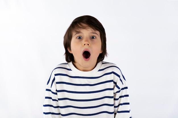 Nahaufnahmeporträt des schockierten beängstigenden überraschten jungen von neun jahren mit einem weit geöffneten mund isoliert