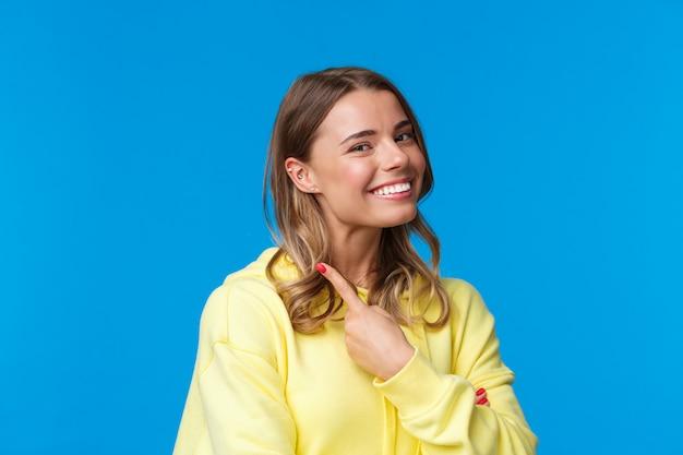 Nahaufnahmeporträt des schönen blonden mädchens mit den kurzen haaren, die auf ihr piercing im ohr zeigen, stolz und zufrieden lächeln, ihren blick ändern, auf einer blauen wand im gelben kapuzenpulli stehend
