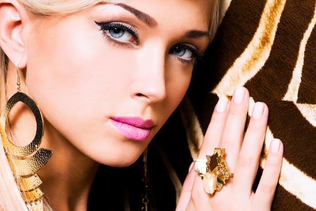 Nahaufnahmeporträt des schönen gesichts der sexy frau mit mode-make-up und goldring am finger