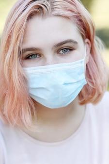 Nahaufnahmeporträt des schönen jungen mädchens bedecken ihr gesicht, das medizinische blaue maske, covid-19-pandemie-infektionskrankheitsausbruchschutz trägt. gesundheitskonzept.