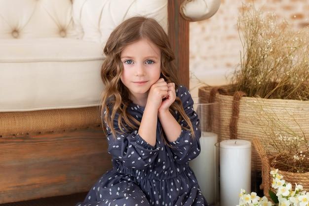 Nahaufnahmeporträt des schönen kaukasischen kleinen mädchens, das kamera mit entzückendem lächeln betrachtet. kindheitskonzept.