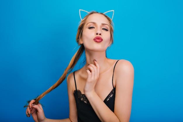 Nahaufnahmeporträt des schönen mädchens, das kuss gibt, partei genießt. langes haar in der hand halten. schwarzes kleid, stirnband mit katzenohren.