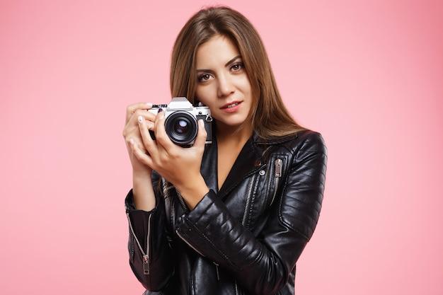 Nahaufnahmeporträt des schönen mädchens, das mit alter filmkamera aufwirft