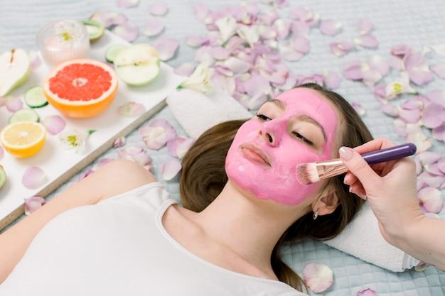 Nahaufnahmeporträt des schönen mädchens, das rosa schlammgesichtsmaske anwendet. spa frau, die gesichtslehmmaske anwendet. schönheitsbehandlungen.