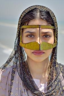 Nahaufnahmeporträt des schönen persischen mädchens in der traditionellen maske von hormozgan, iran.