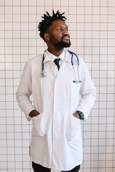 Nahaufnahmeporträt des schwarzen doktors, der kamera lächelt und betrachtet.