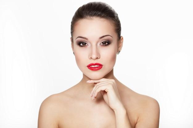 Nahaufnahmeporträt des sexy kaukasischen jungen frauenmodells mit glamourösen roten lippen, hellem make-up, augenpfeil-make-up, reinem teint. perfekt saubere haut.