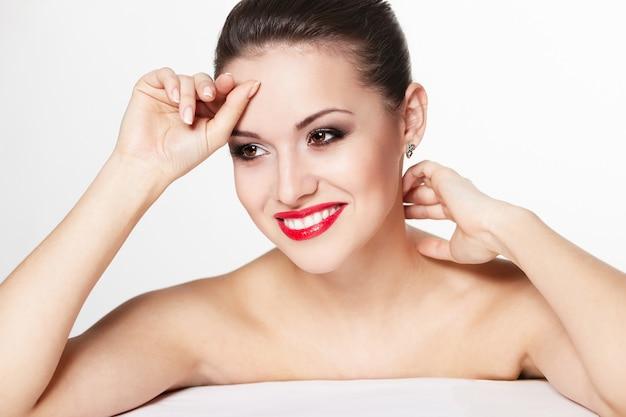 Nahaufnahmeporträt des sexy lächelnden kaukasischen jungen frauenmodells mit glamourösen roten lippen, hellem make-up, augenpfeil-make-up, reinem teint. perfekt saubere haut. weiße zähne