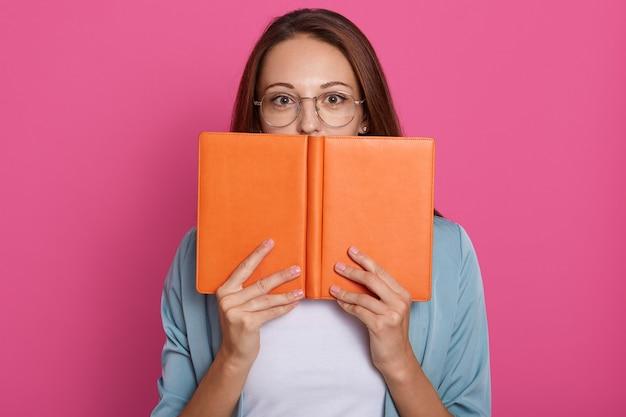 Nahaufnahmeporträt des studentenmädchens versteckt sich hinter buch, studiofoto über rosa