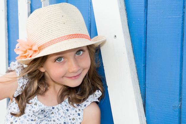Nahaufnahmeporträt des tragenden strohs des entzückenden lächelnden kindermädchens blüht hut