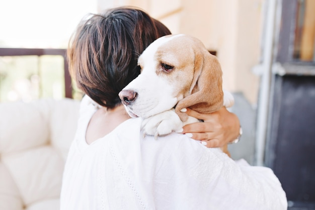 Nahaufnahmeporträt des traurigen beagle-hundes, der weg über schulter des brünetten mädchens schaut