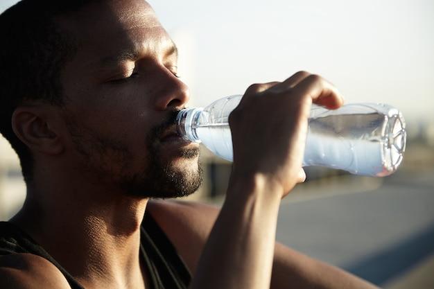 Nahaufnahmeporträt des trinkwassers des jungen bärtigen mannes