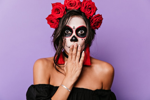Nahaufnahmeporträt des überraschten mädchens mit braunen augen und make-up für halloween. erwachsene frau mit rosenkrone bedeckt ihren mund mit der hand vor schock.