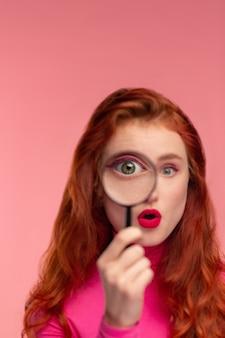Nahaufnahmeporträt des überraschten rothaarigen mädchens, das kamera durch lupe betrachtet