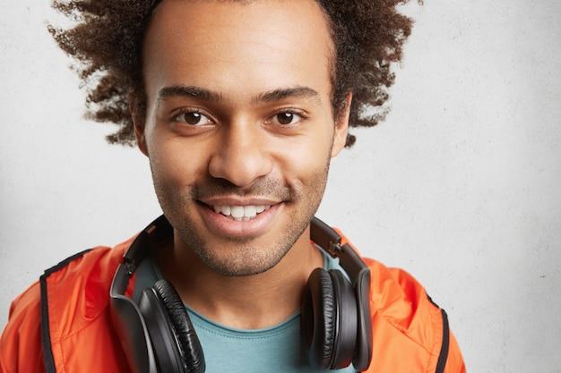 Nahaufnahmeporträt des unrasierten hübschen jungen hipster-kerls schaut mit den dunklen leuchtenden augen und erfreutem lächeln