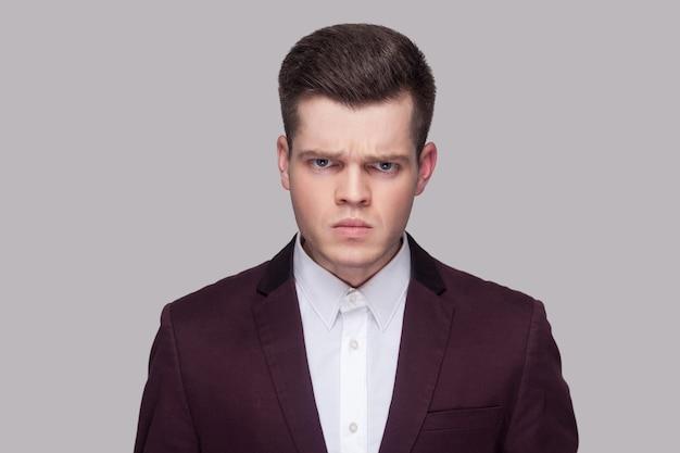 Nahaufnahmeporträt des verärgerten hübschen jungen mannes im violetten anzug und im weißen hemd, der kamera mit aggressiver schlechter laune steht und betrachtet. indoor-studioaufnahme, auf grauem hintergrund isoliert.