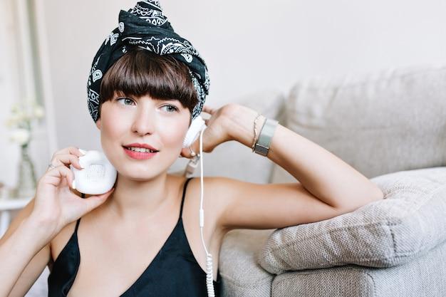 Nahaufnahmeporträt des verträumten brünetten mädchens mit dem trendigen band im haar, das weg schaut, während musik hört