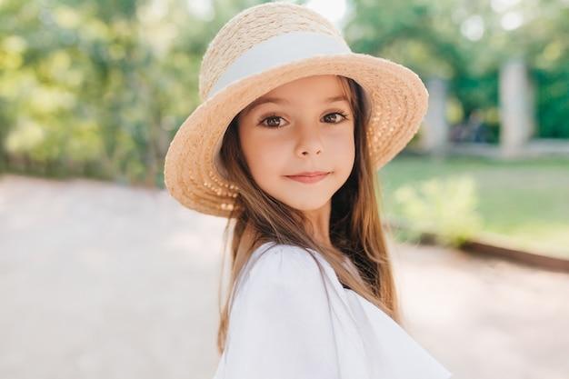 Nahaufnahmeporträt des wundervollen kindes mit glänzenden braunen augen, die mit interesse schauen. enthusiastisches kleines mädchen im weinlesestrohhut verziert mit band, das während des spiels im park aufwirft.