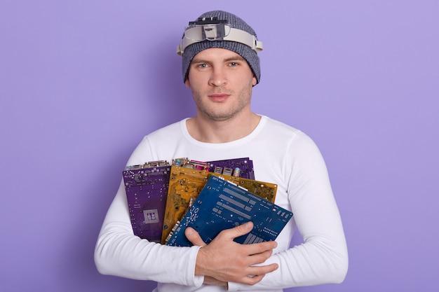 Nahaufnahmeporträt des zuversichtlichen intelligenten elektronischen ingenieurs, der drei bunte elektronische leiterplatten hält