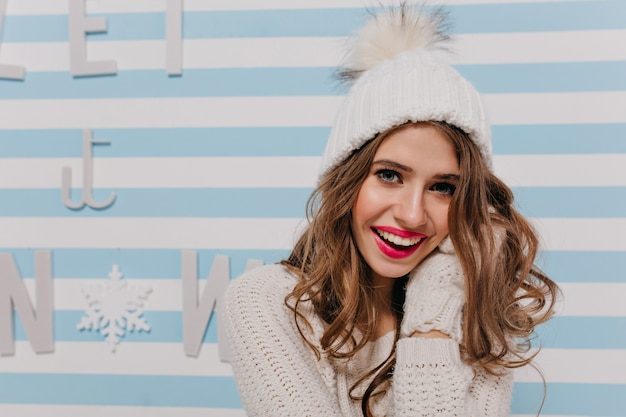 Nahaufnahmeporträt drinnen des mädchens mit weit geöffneten blauen augen und schneeweißem lächeln. junges modell im weißen warmen hut posiert glücklich auf gestreifter wand