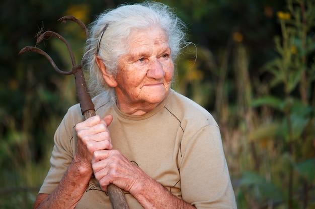 Nahaufnahmeporträt einer alten frau mit dem grauen haar, das eine rostige heugabel oder einen zerhacker in ihren händen, gesicht in den tiefen falten hält