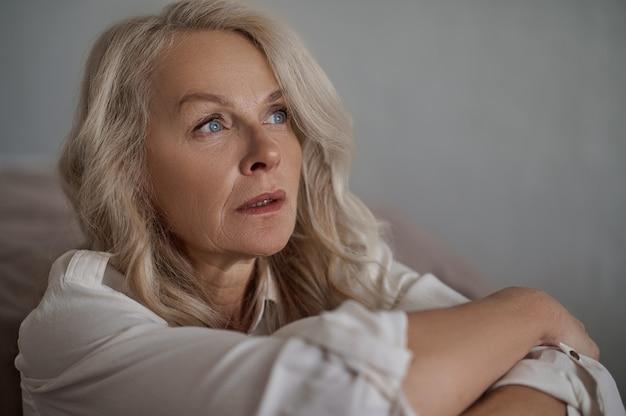Nahaufnahmeporträt einer attraktiven blauäugigen reifen traurigen dame mit einem weit entfernten blick, der wegschaut
