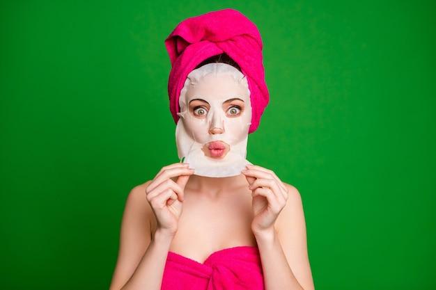 Nahaufnahmeporträt einer attraktiven, fassungslosen dame mit turban, die die gesichtsglättungsmaske-therapie-schmollenlippen isoliert auf hellgrünem hintergrund entfernt