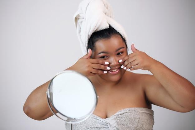 Nahaufnahmeporträt einer attraktiven jungen frau, die creme auf ihrem gesicht anwendet.