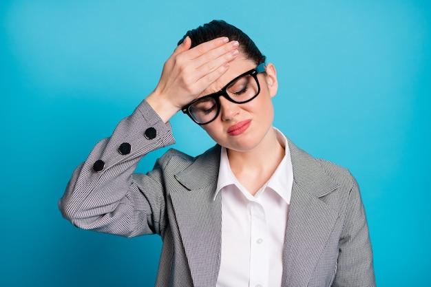 Nahaufnahmeporträt einer attraktiven, kranken, depressiven, müden dame, die sich schlecht an der stirn fühlt, einzeln auf hellblauem hintergrund