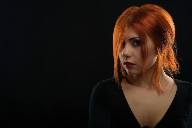 Nahaufnahmeporträt einer attraktiven roten behaarten jungen frau, die mysteriös schaut