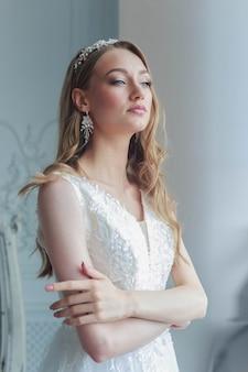 Nahaufnahmeporträt einer braut in einem weißen hochzeitskleid schaut aufmerksam beiseite.