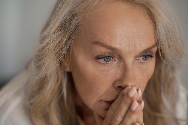 Nahaufnahmeporträt einer depressiven blauäugigen attraktiven blonden frau, die ihre gefalteten hände an ihren mund drückt