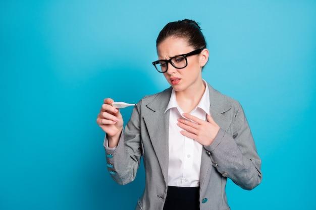 Nahaufnahmeporträt einer depressiven verzweifelten dame, die die körpertemperatur einzeln auf hellblauem hintergrund misst