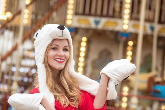Nahaufnahmeporträt einer entzückenden blonden frau mit lustigem hut, die in der nähe des karussells mit lichtern posiert