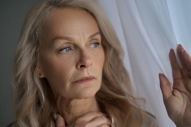Nahaufnahmeporträt einer ernsten besorgten frau, die einen fenstervorhang berührt und in die ferne starrt
