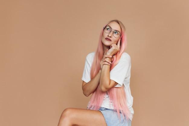 Nahaufnahmeporträt einer erstaunten hübschen jungen frau mit brille und rosa haaren im weißen hemd, die mit dem finger zeigt, einzeln auf beigem hintergrund.