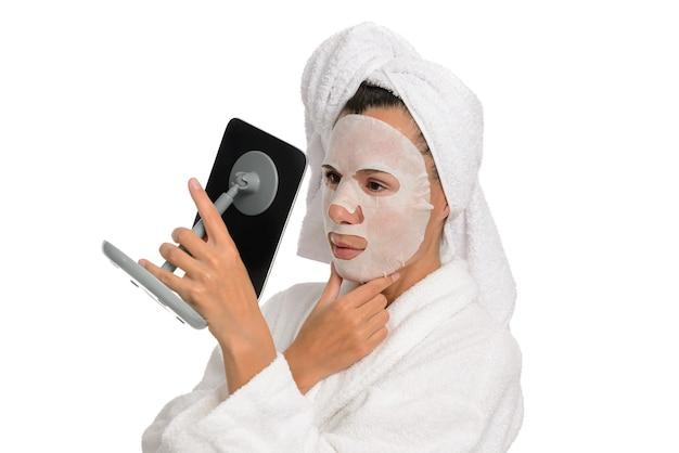 Nahaufnahmeporträt einer frau, die im spiegel auf ihrem gesicht eine feuchtigkeitsspendende kosmetische maske schaut