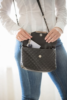 Nahaufnahmeporträt einer frau, die schlüssel aus der handtasche nimmt
